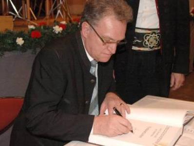 Landrat Gebhard Kaiser trägt sich in das Ehrenbuch der Gemeinde Mittelberg ein.