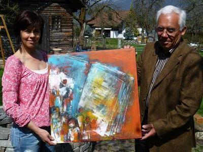 M. Gabriel schenkt A. Hartmann ein Bild, das ersteigert werden kann.