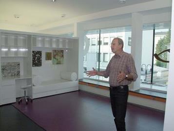 Architekt Angelo Roventa vor seiner mobilen Wohnzimmerwand