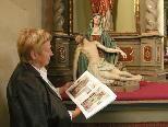Bild: Pfarrkirchenrätin Hannelore Wehinger mit dem neuen Buch vor dem linken Altar in der Alten Kirche.