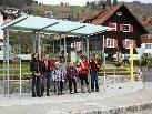 """Fahrgäste freuen sich über das neue Buswartehäuschen bei der Haltestelle """"Dorfplatz""""."""
