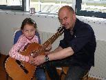 Musiklehrer erklären den Besuchern beim Tag der offenen Tür die Instrumente.