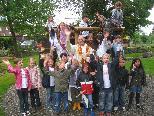 Zusammen mit Pfarrer Gerhard Mähr freuen sich die Kinder über ihren neuen Spielplatz.