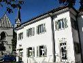 """Im ehemaligen """"Kooperatorhaus"""" der Pfarre ist der Verein """"Domino s'Hus am Kirchplatz"""", die Spielgruppe """"Sonnenschein"""", die Bibliothek und der Weltladen untergebracht."""