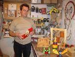 Johannes Gangel präsentiert in seiner Werkstatt im Keller einige bunte Werkstücke, darunter auch Spielzeug zum lernen.