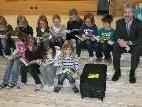 Die Schüler der Volksschule Egg, mit Bankdirektor Rehm, bedienten sich gleich aus dem Bücherkoffer.