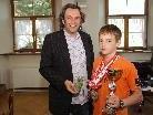 Bürgermeister Michael Tinkhauser gratulierte dem Schwimmtalent und überreichte RFI-Münzen.