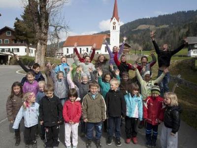 Der Sibratsgfäller Nachwuchs: Volksschüler und Kindergärtler in Aktion. Im Hintergrund die Pfarrkirche Sibratsgfäll.