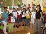 Stolz präsentieren die Schüler(innen) mit Lehrerin Evi Gaiser (l.) und Initiatorin Wilma Schneller ihren Bibliotheksführerschein.