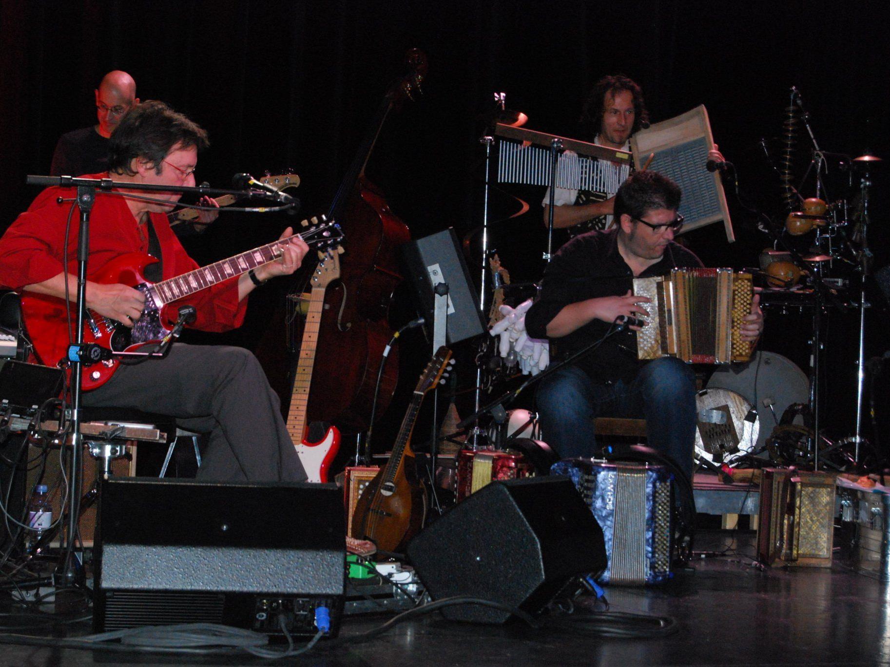 Max Lässer an der Gitarre mit Ausschnitt des Orchesters.