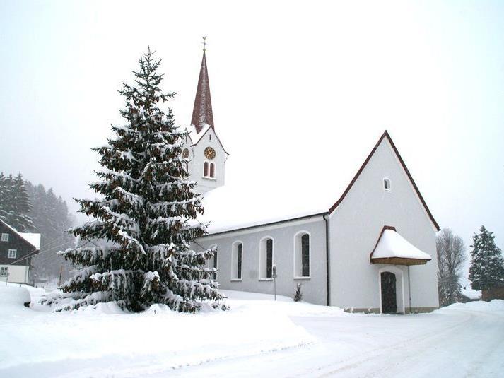 Ein Weihnachtsbaum mit vielen Tannenzapfen vor der tief verschneiten Pfarrkirche von Sibrtagsgfäll