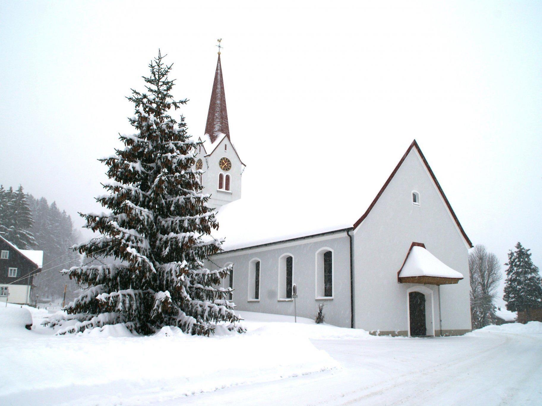 Ein Christbaum mit vielen Tannenzapfen vor der tief verschneiten Pfarrkirche in Sibratsgfäll lässt Weihnachtsstimmung aufkommen.