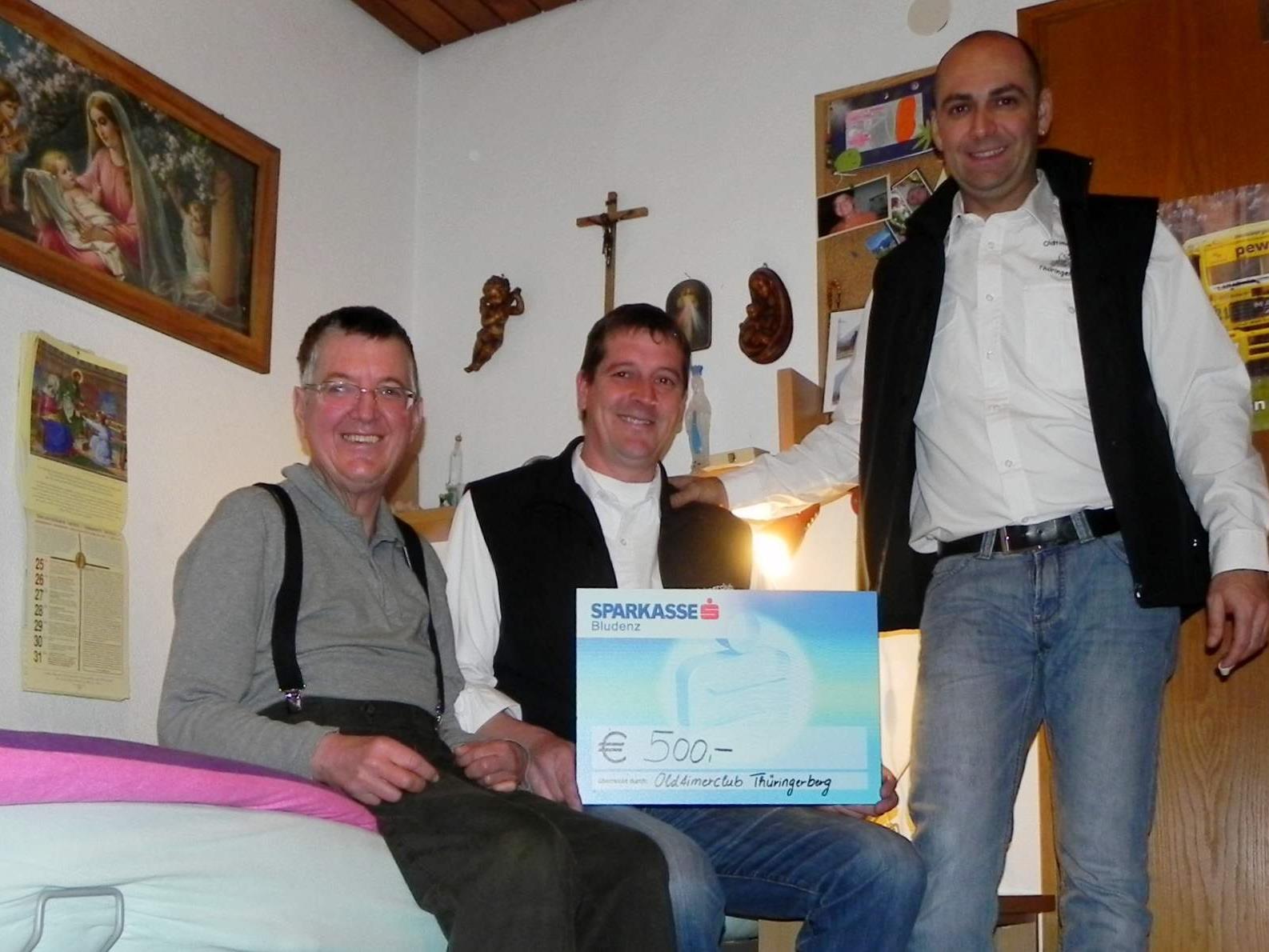 Günter Konzett und Peter Handlos bei der Scheckübergabe an Mario.