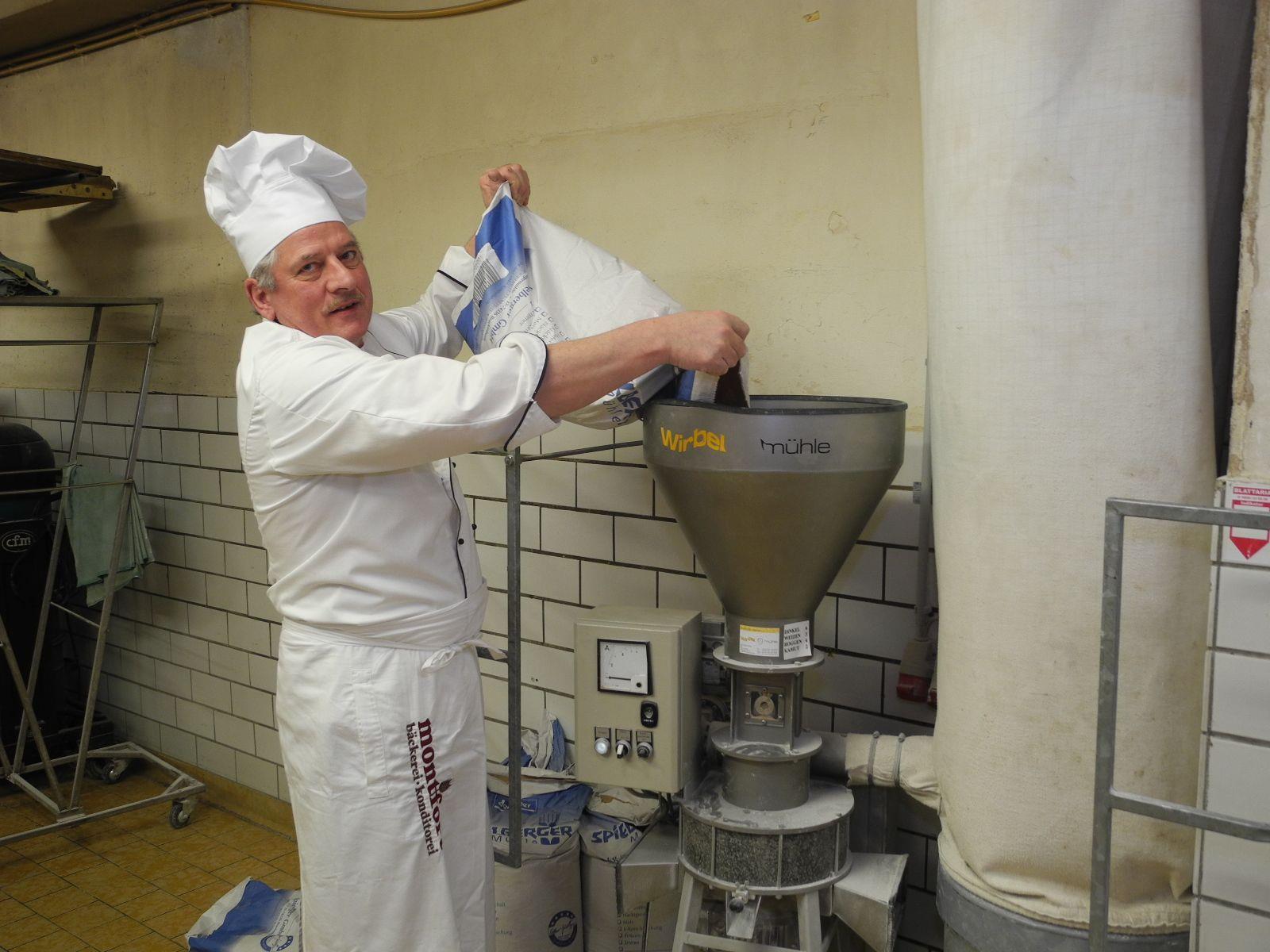 Manfred Kuster befüllt die Wirbel-Mühle mit Dinkelgetreide