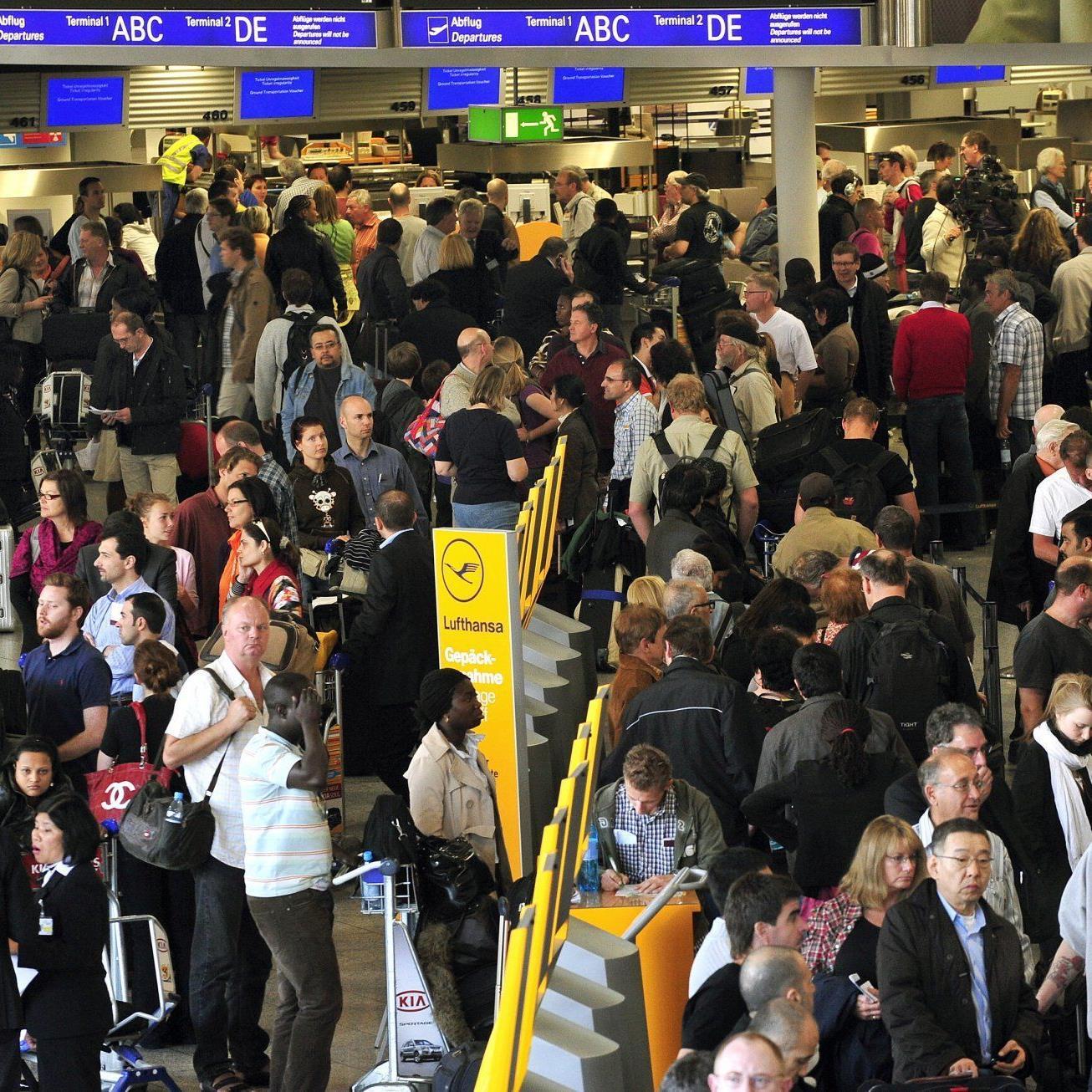 Dutzende Flugpassagiere warten am Frankfurter Flughafen in langen Schlangen vor den Schaltern.
