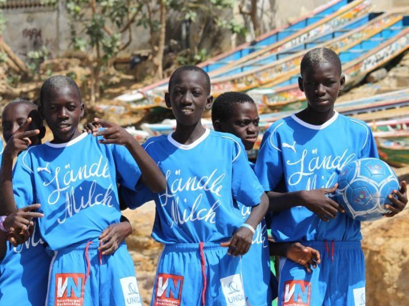 Glückliche Sportsfreunde aus dem Senegal mit den FC-Blau-Weiß-Dressen.