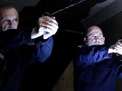 Polizisten, die bei einer Einsatzübung für den Ernstfall den Gebrauch von Schusswaffe und Pfefferspray üben