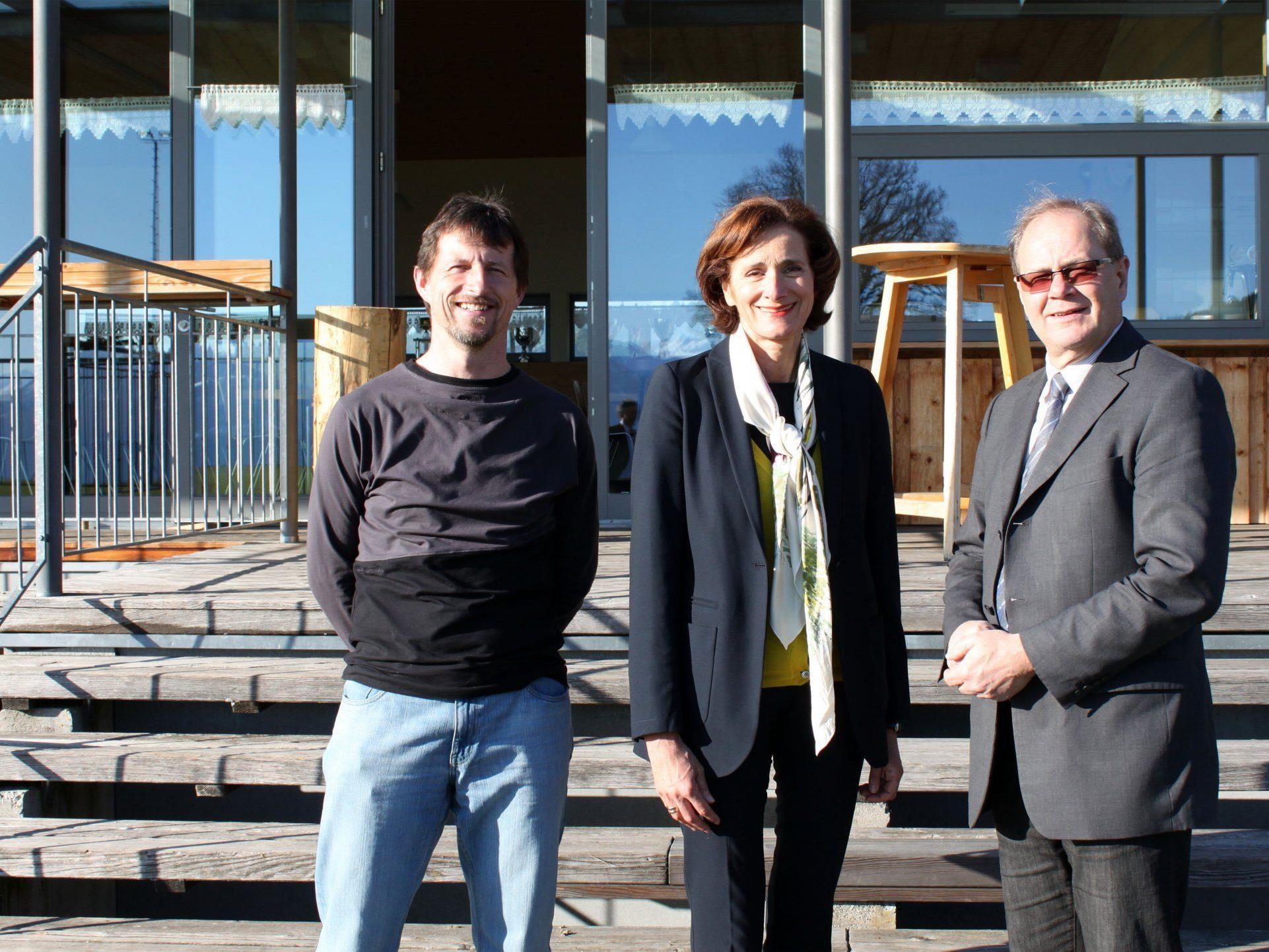 LTP Bernadette Mennel mit Bgm. Reinhard Nachbaur und Hugo Kathan vom FC Fraxern vor dem Clubhaus am höchstgelegenen Fußballplatz Vorarlbergs
