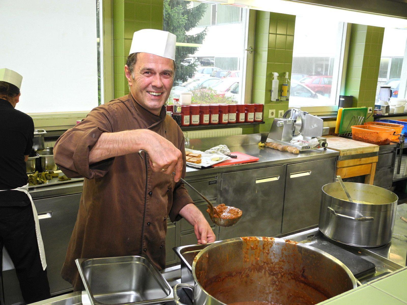 Chefkorch Thomas Wachter beim Schöpfen der Speisen