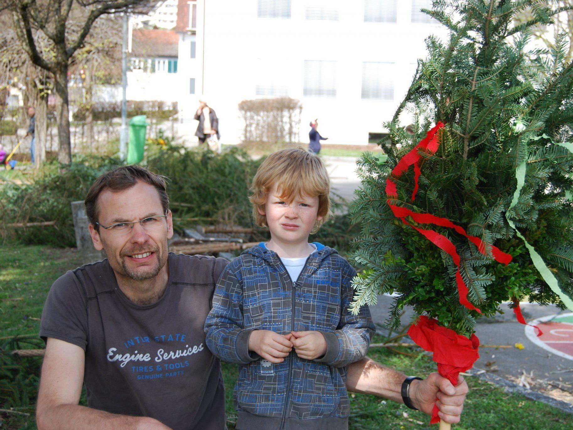 Vater und Sohn sind stolz auf ihren selbst gefertigten Palmen.