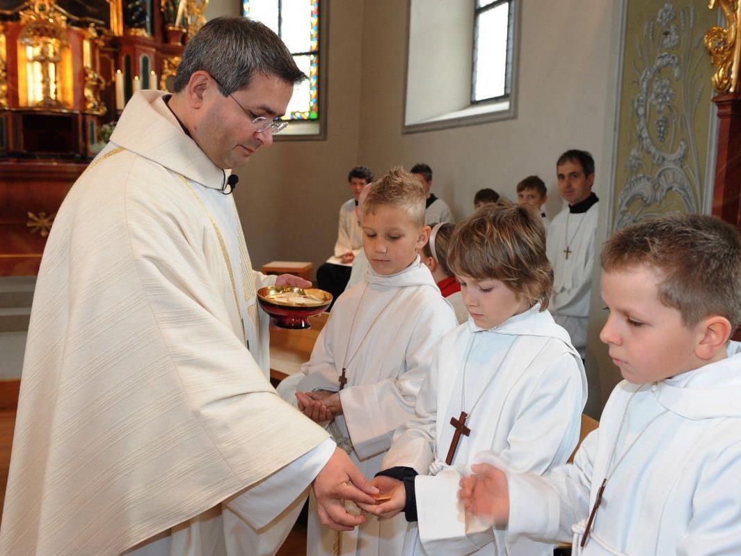 Ein großer Moment: Die Kinder empfangen erstmals den Leib Christi.