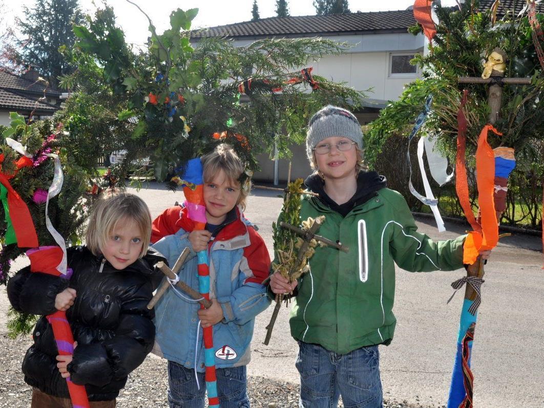 Laura, Noah und Elias freuen sich über ihre schönen Palmen, die am Sonntag vor dem Einzug in die Kirche gesegnet wurden.