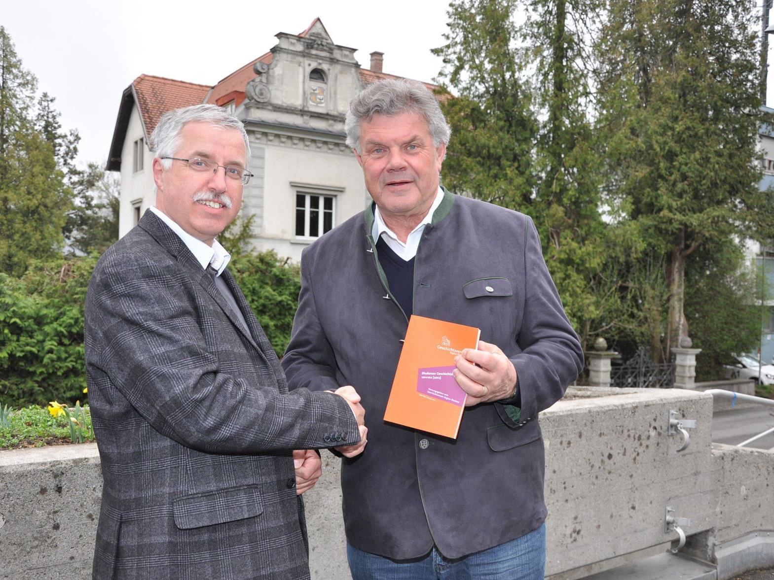Der Obmann des Geschichtsvereins Region Bludenz, Otto Schwald, überreicht Bürgermeister Mandi Katzenmayer das druckfrische Doppelheft Nr. 101/102)