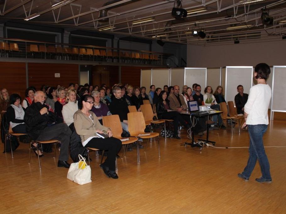 Die Zuschauer lauschen gespannt dem Vortrag von Fr. Troy
