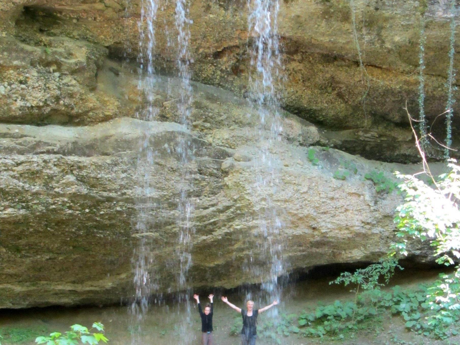 Hinter einem Wasserfall führt der Weg vorbei - ein feiner Wassernebel umfängt die Besucher