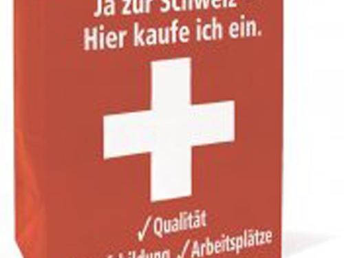 """Mit dieser roten Papiertragtasche mit Schweizer Kreuz will der SVG die Schweizerinnen und Schweizer zum Nachdenken über das """"System Schweiz"""", anregen."""