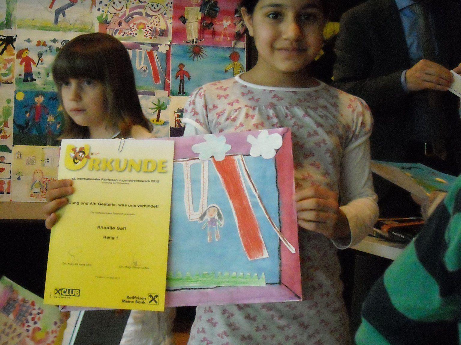 """Khadija mit ihrem Bild """"Mama macht Spaß""""."""