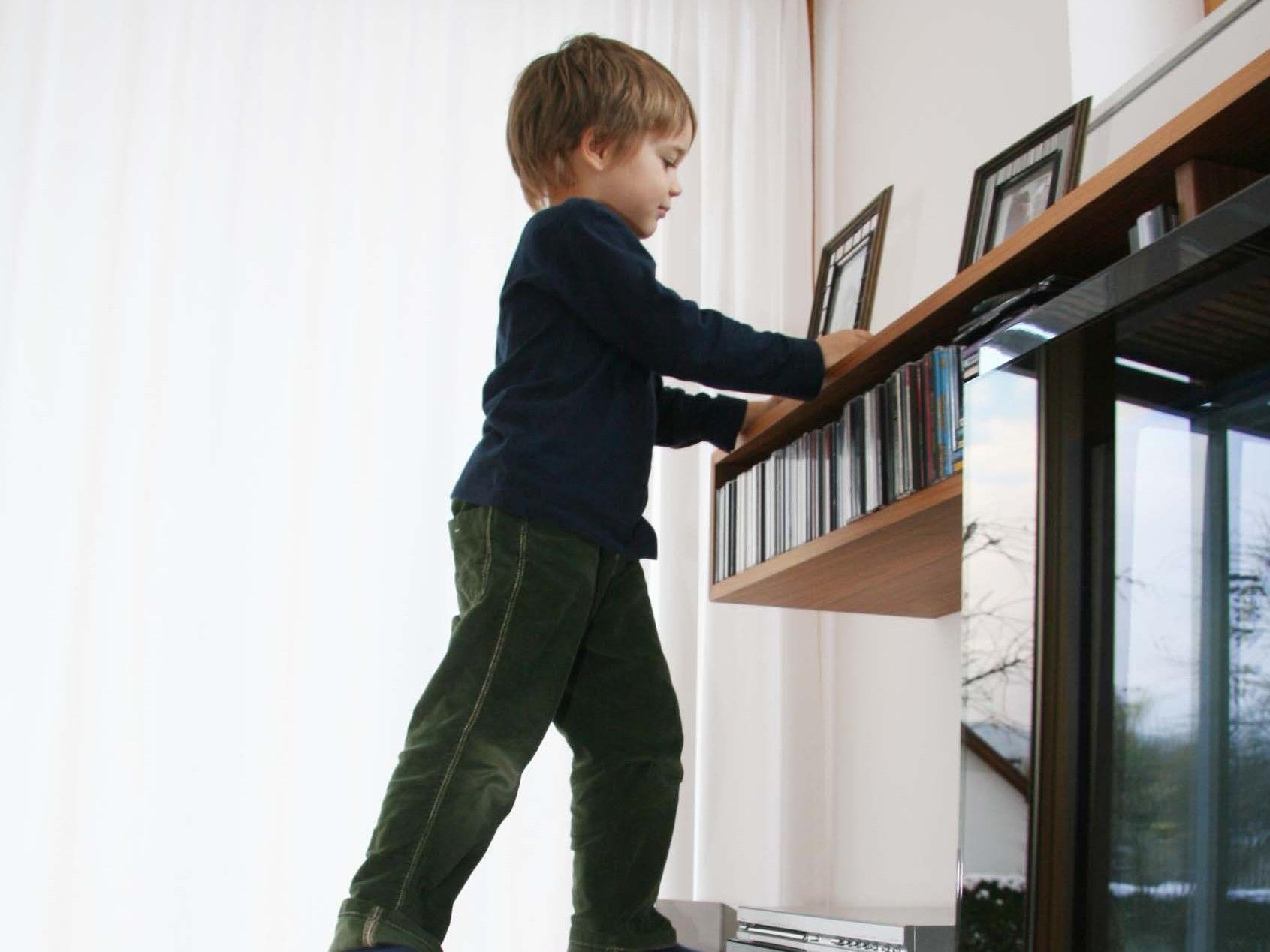 Ein Junge erprobt seine Geschicklichkeit beim Klettern im Wohnbereich.