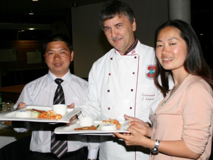 """Küchenmeister Schneider, Vizedir. Rongping, Lehrerin Ye Xiaoni servieren """"Menü im Doppelpack"""" – chinesisch und wälderisch."""