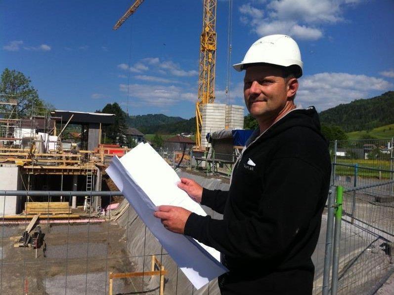Baupolier Dietmar Kohler erläutert die Fortschritte der Bauarbeiten am Werkraumhaus in Andelsbuch.