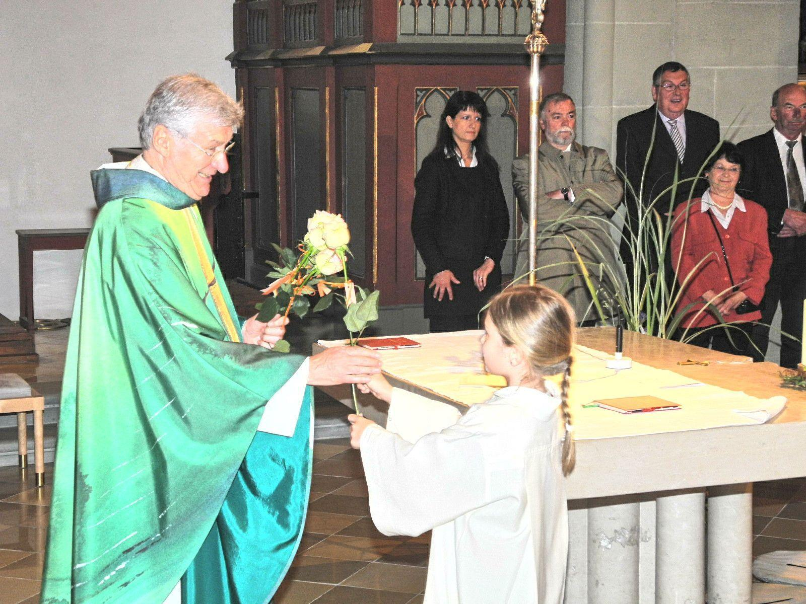 Eine Ministrantin überreicht Dompfarrer Rudolf Bischof eine Rose