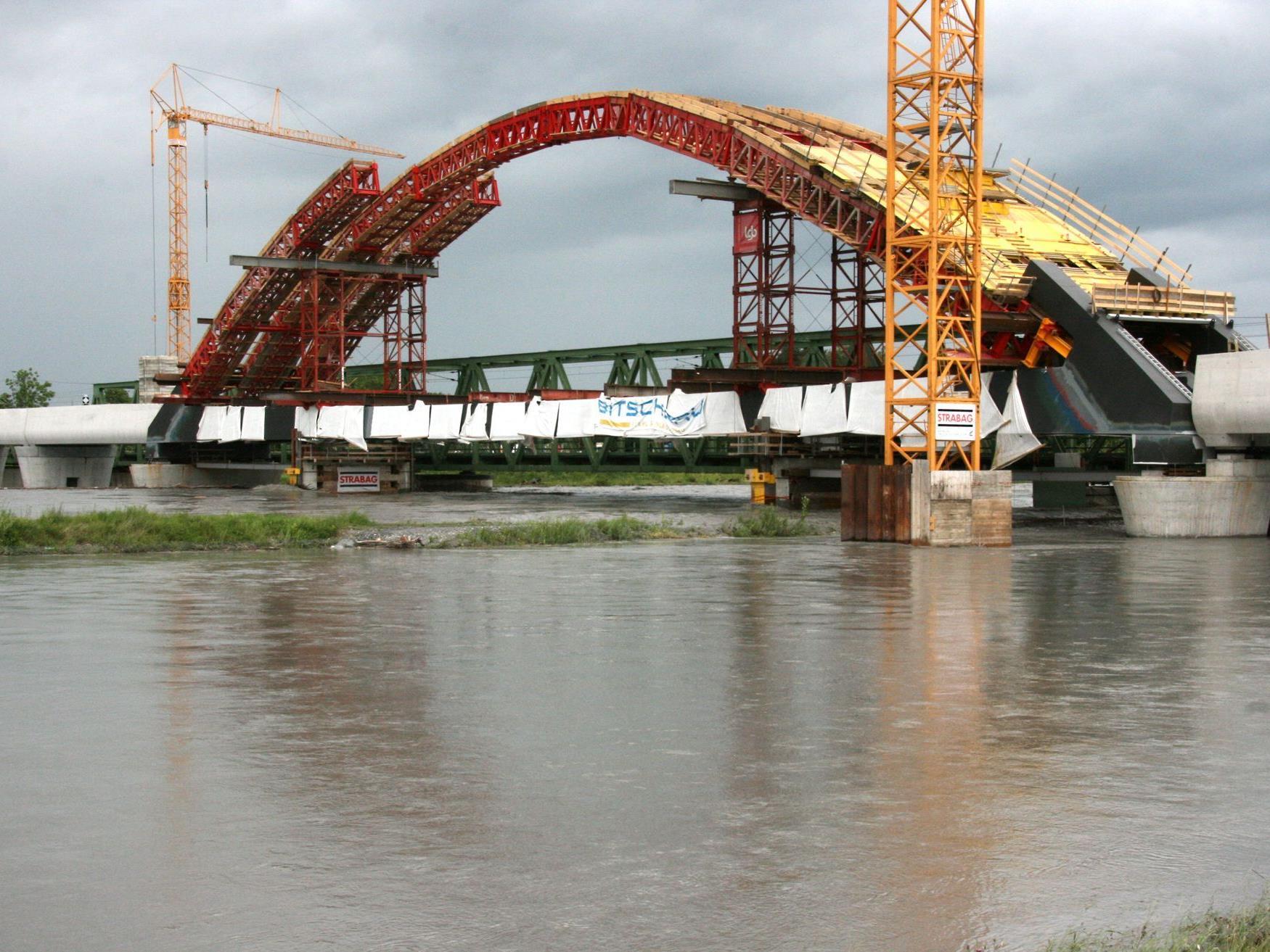 Die neue Rheinbrücke nimmt Form an, momentan stoppt der Hochwasser führende Rhein die Bauarbeiten.