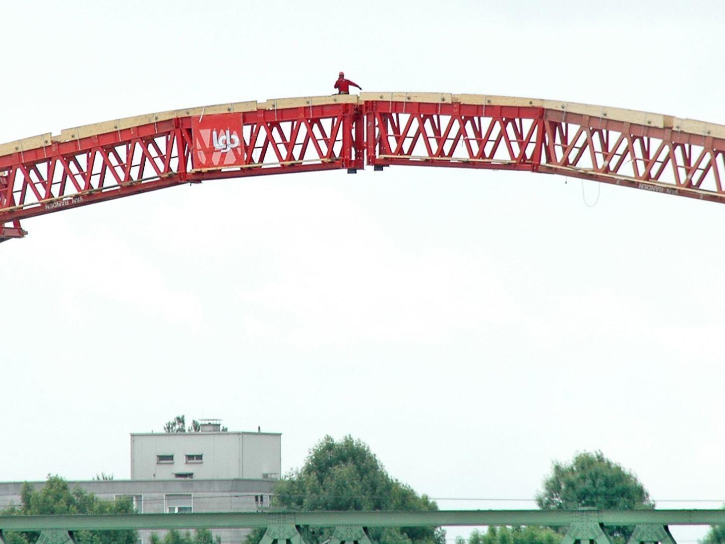 In luftiger Höhe werden die Gerüste für die Bogenbrücke über den Rhein miteinander verbunden.