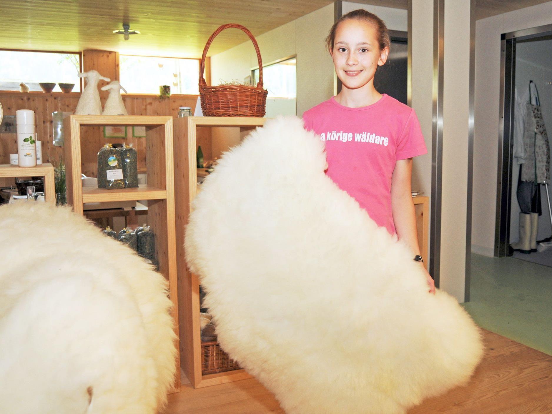 Verena mit einem weichen Fell aus dem Schafzuchtbetrieb ihrer Eltern in Bizau.