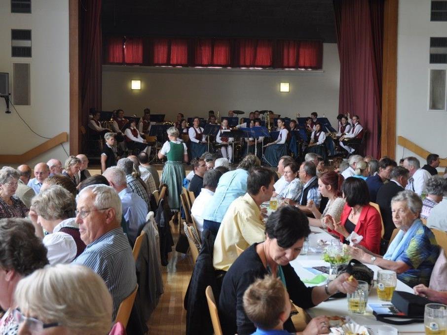 Vollbesetzte Tische beim Dorffest im Gemeindesaal.