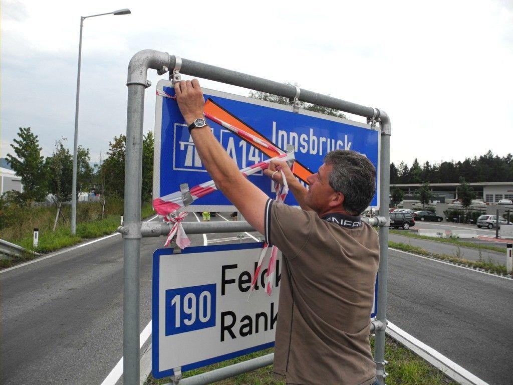 Wolfgang Lassnig von der Straßenbauabteilung entfernt die Bänder von den Straßenhinweistafeln und übergibt damit die neue Frutzbrücke den Autofahrern.
