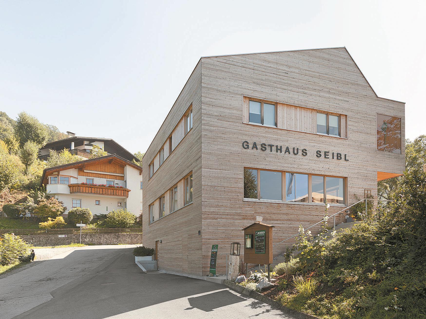 Giebelständig zum Hang wie die Nachbarschaft – ohne Lederhosenarchitektur. Mit markantem asymmetrischem Dach wegen des gemeinsamen Giebels und der angehängten Loggia.