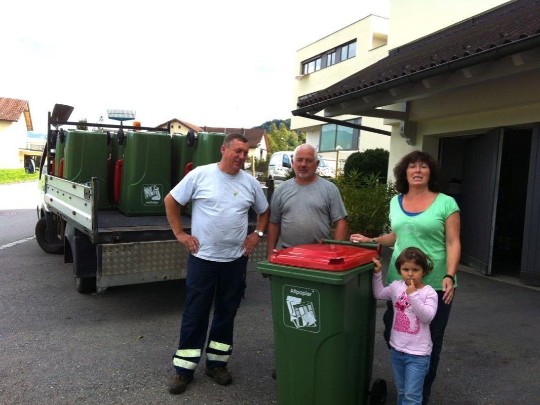 Die Gemeindearbeiter Aladin und Helmut liefern die Kunststofftonne mit 240 Litern Volumen bei Familie Rita Morscher und Mia ab