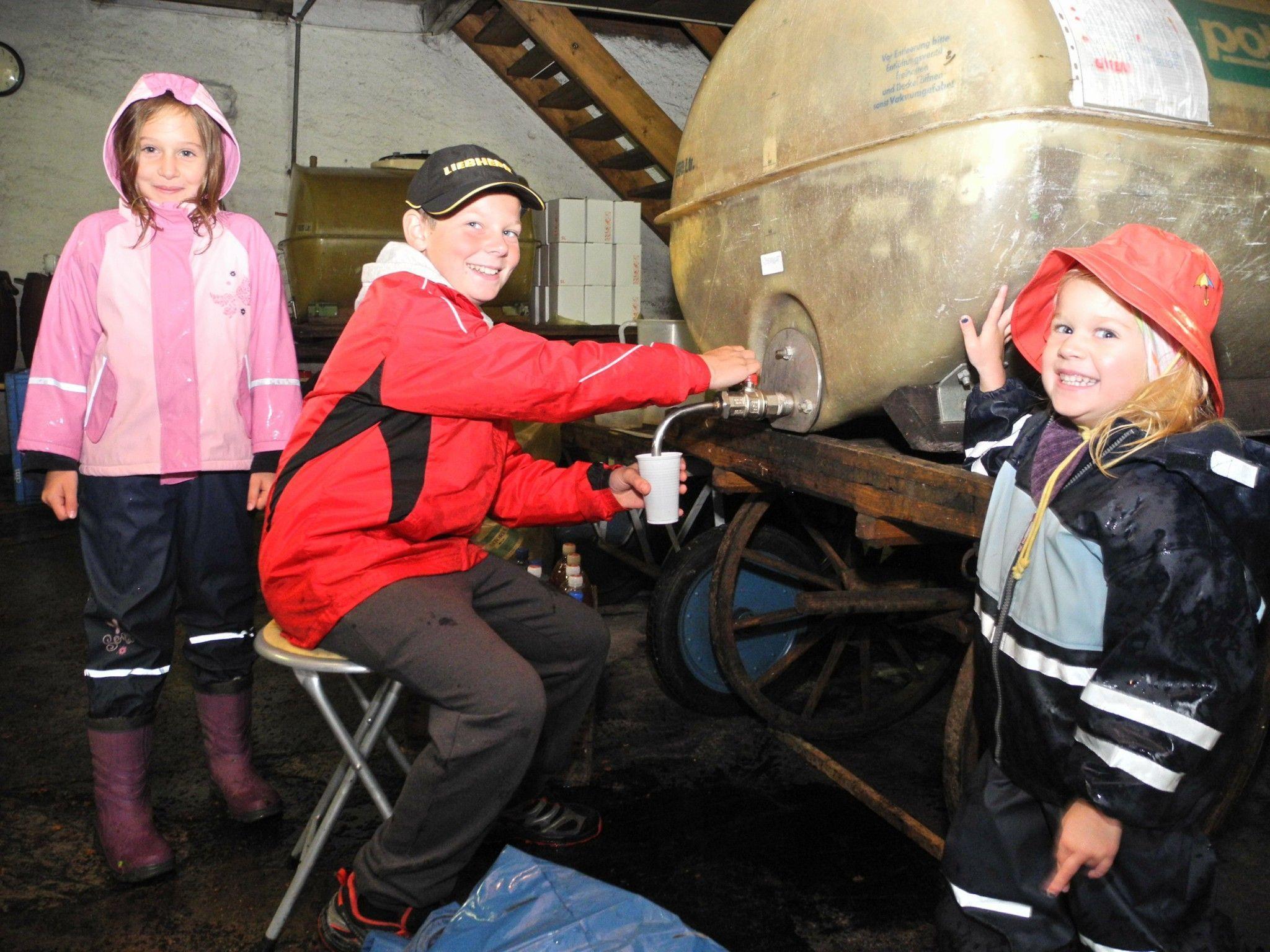 """(l.) Anna-Christine, Lukas und Antonia genießen den frischen Saft, Lukas schenkt den """"Damen"""" als Kavalier gerne Saft vom Fass ein"""