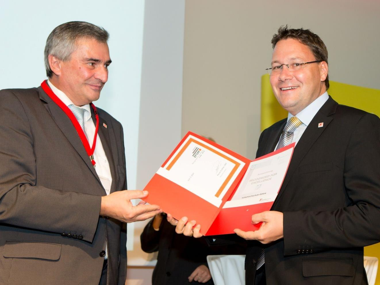 VHS Geschäftsführer Mag. Stefan Fischnaller nimmt von Vertretern der Quality Austria die Auszeichnung entgegen.