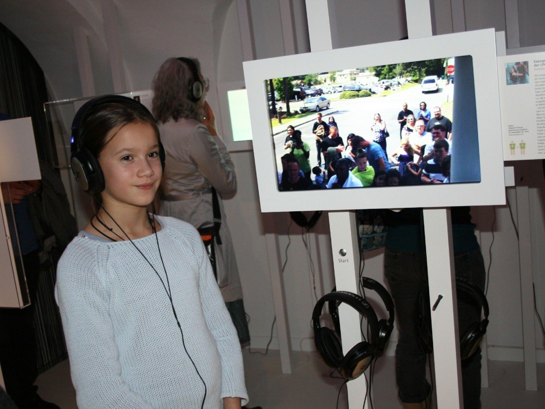 Naima hört sich die Lebensgeschichten in der Ausstellung an.