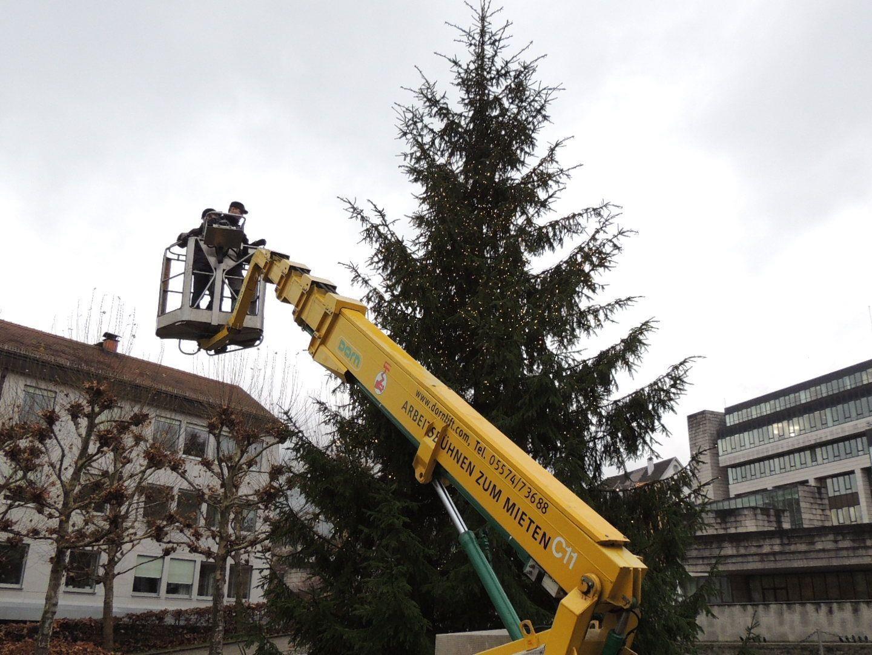 Landhaus Mitarbeiter sorgen für einen festlichen Christbaum vor dem Landhaus