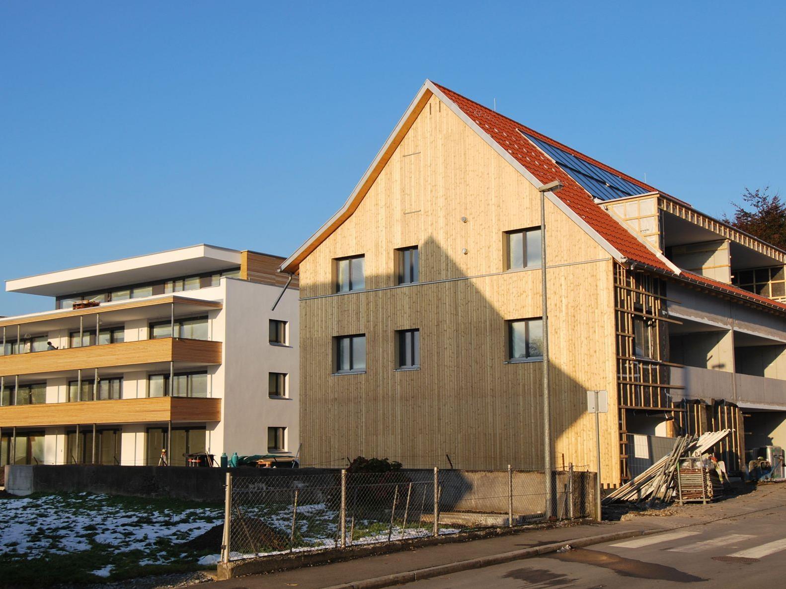 Eines der Gebäude weist ein Satteldach und eine holzverkleidete Fassade auf
