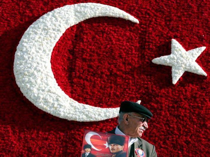 Dieser Mann mit einem Bild von Atatürk trägt einen Mütze - und verstösst damit gegen das Gesetz.