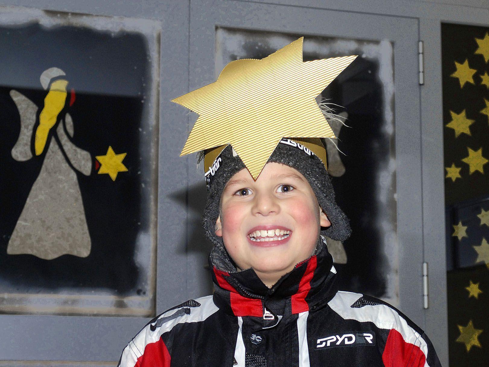 Volksschüler Danny posiert hier vor dem Adventfenster der Volksschule Gantschier