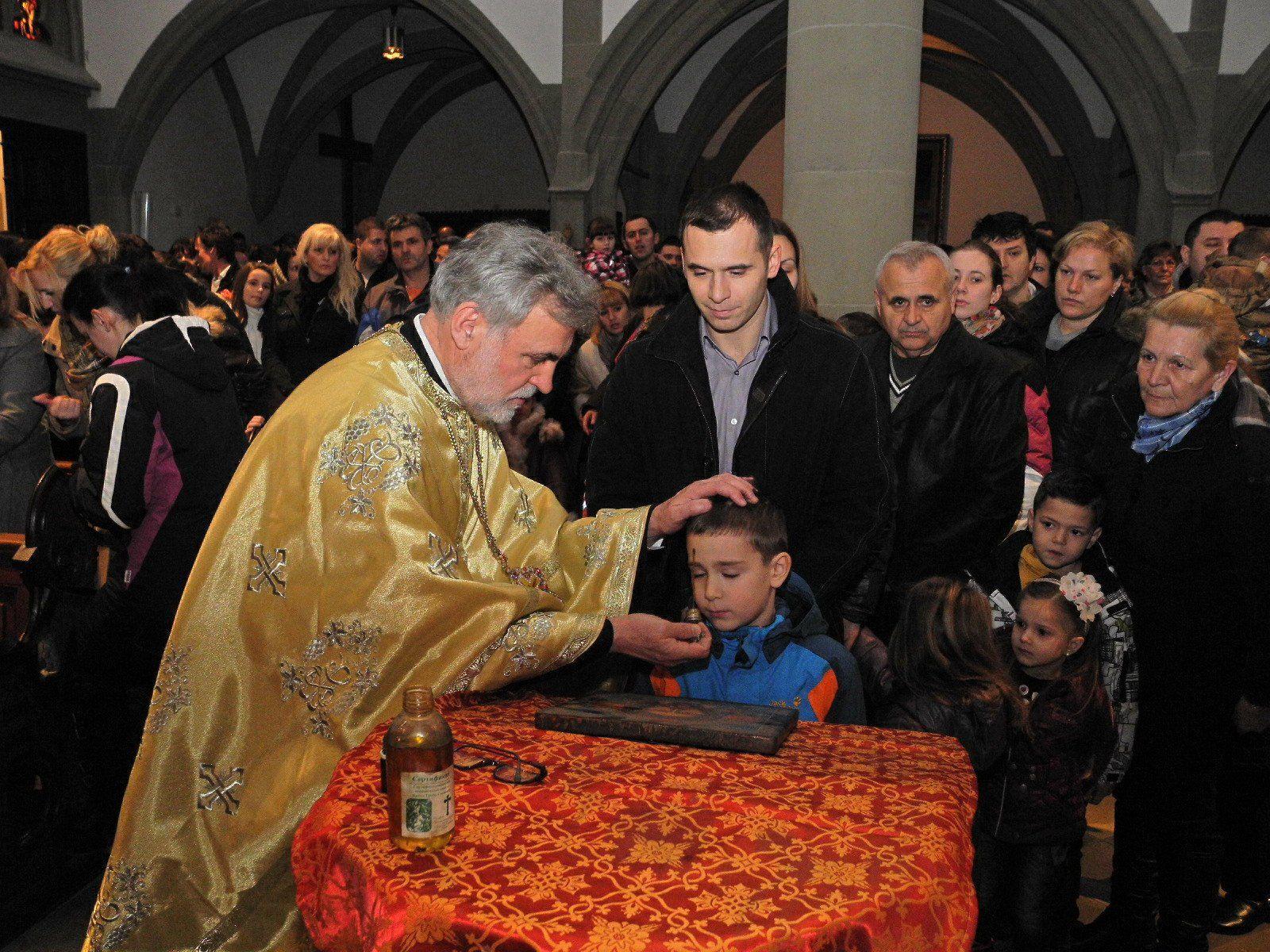 Erzpriester Mile Mijic zeichnete mit Öl ein Kreuz auf die Stirn aller Kirchenbesucher